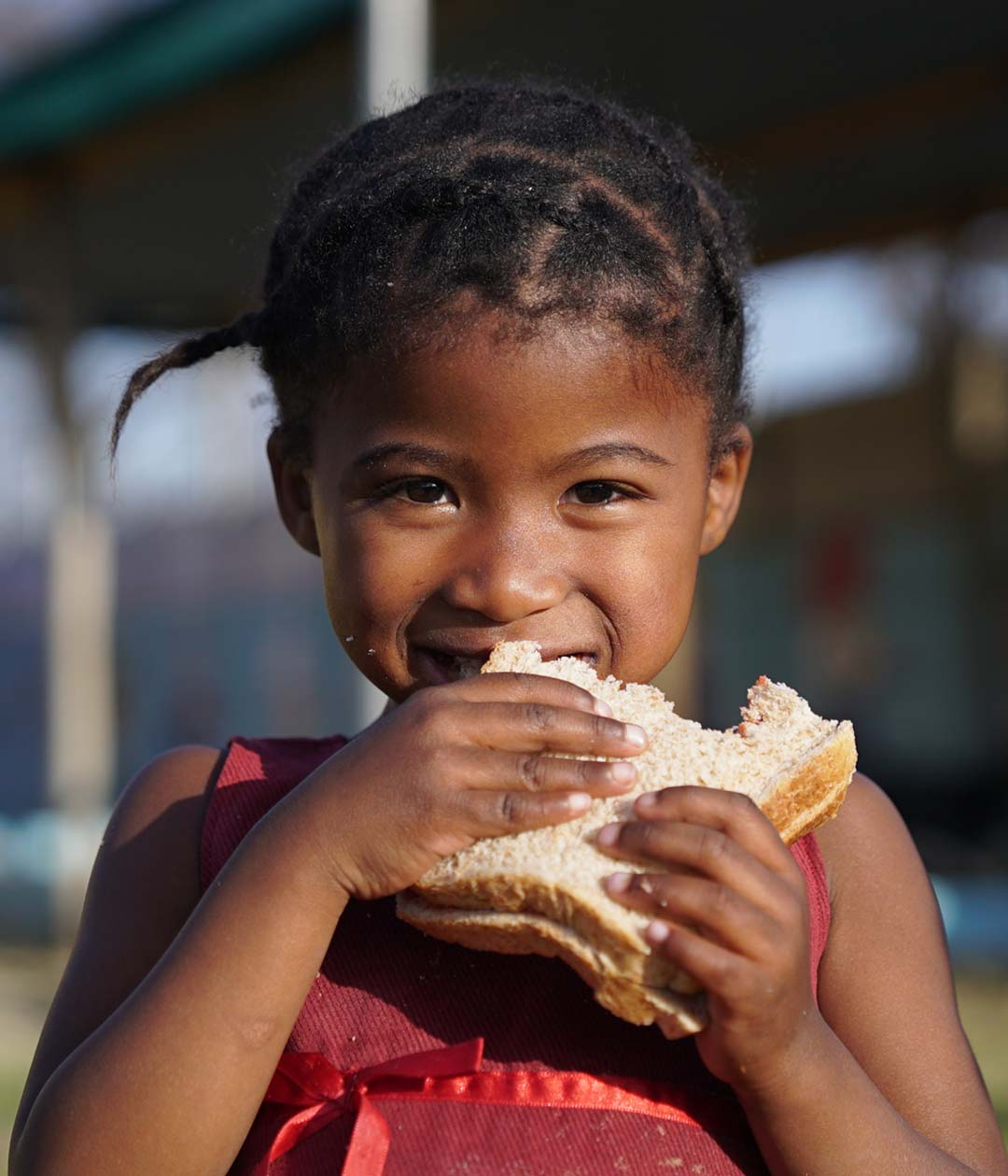Close up of smiling young girl eating a sandwich provided to her by Ladles of Love