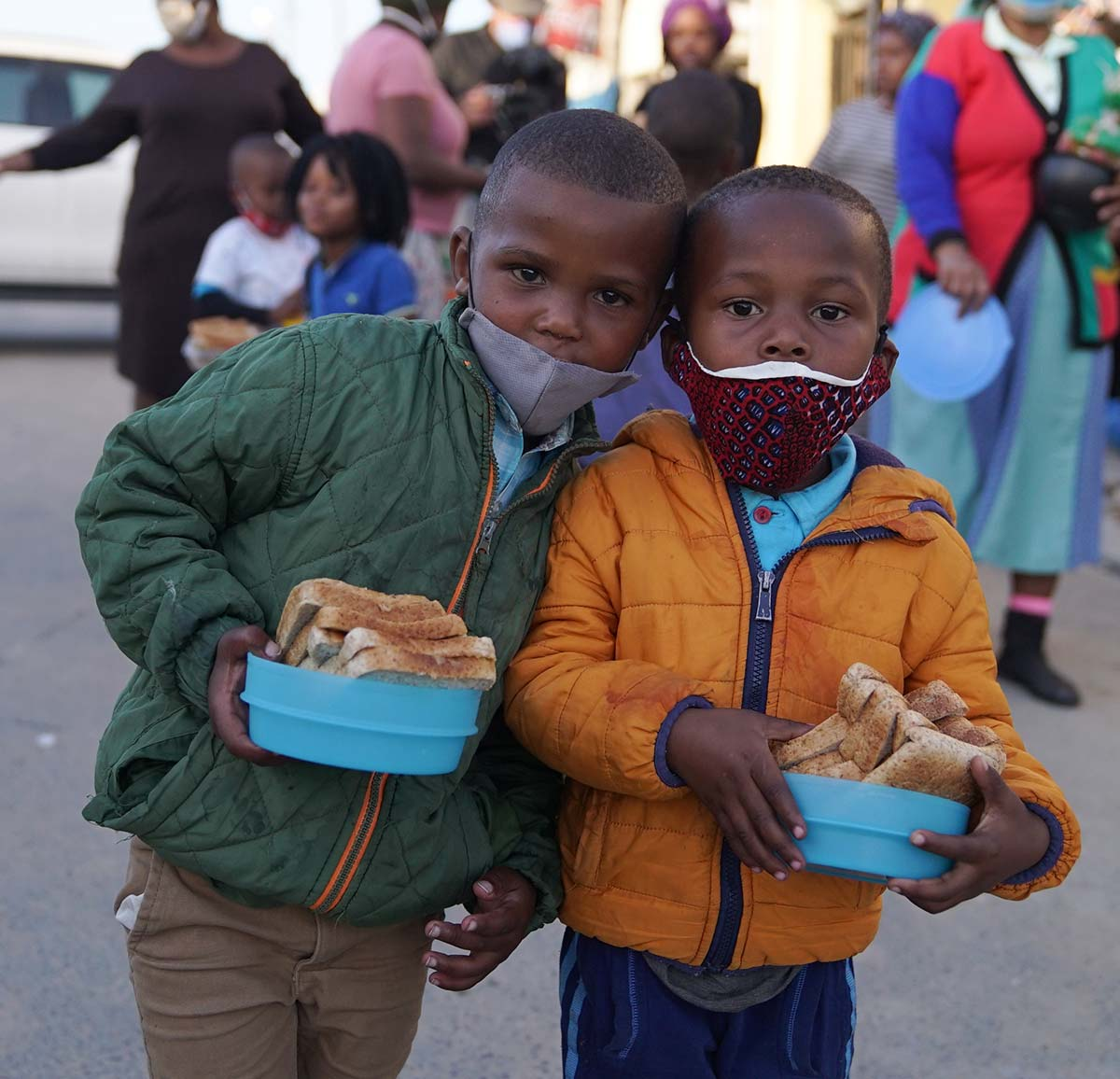Two little boys wearing facemasks holding sandwiches provided by Ladles of Love