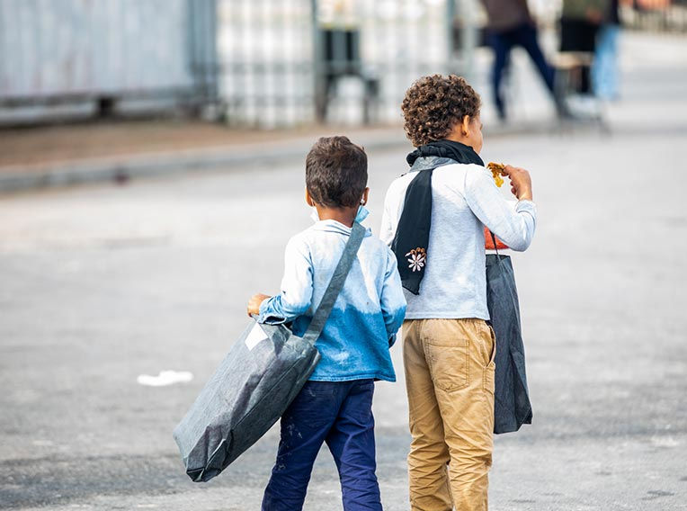 Two boys with their backs to the camera eating the food they've received at soup kitchen
