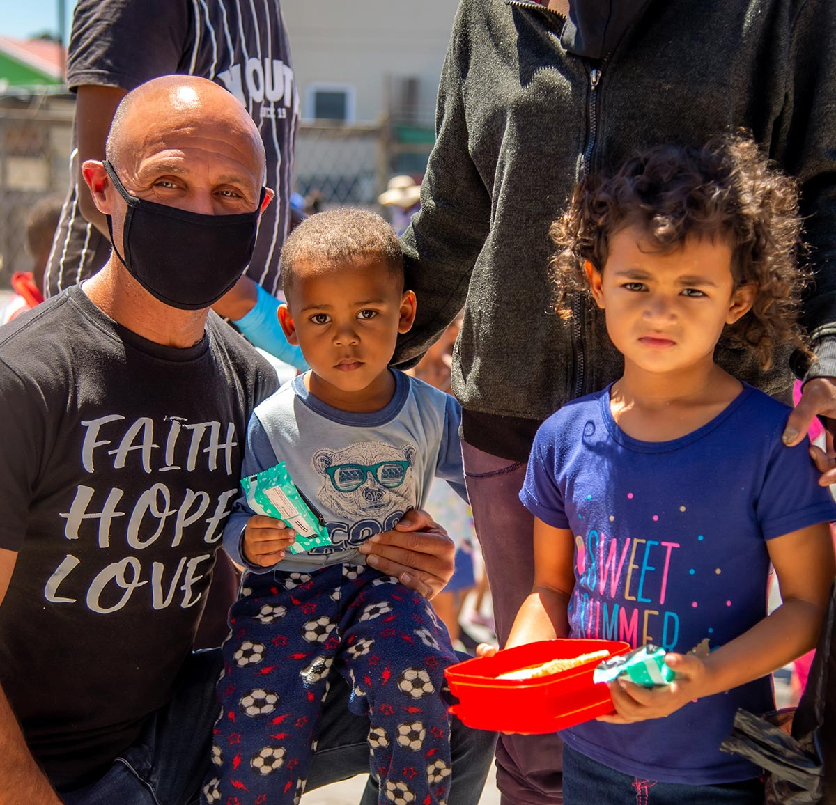 Ladles of Love founder, Danny Diliberto, sits with two young guests at a soup kitchen as they receive their food