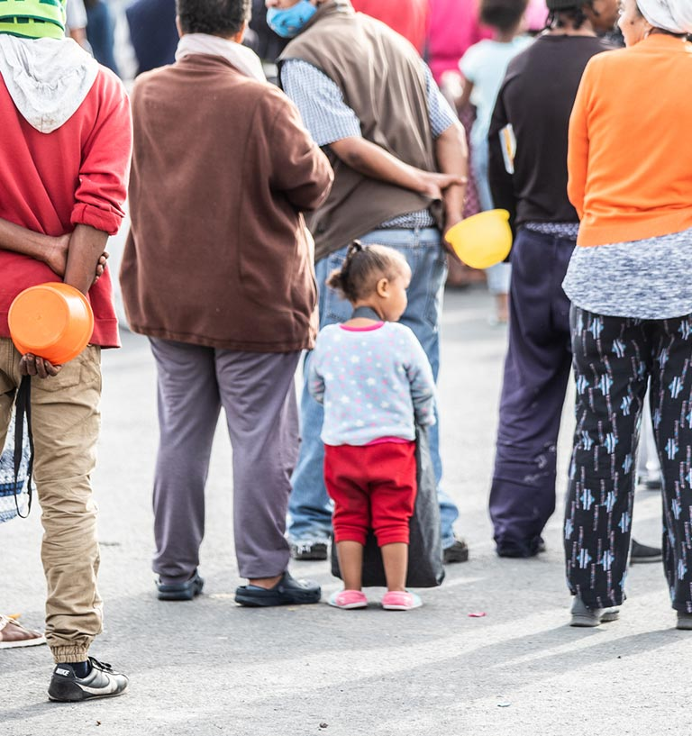 Small child is surrounded by adults holding empty bowls as they queue for food at a soup kitchen