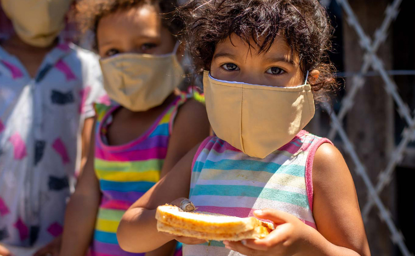 Small child at a soup kitchen wearing a facemask and holding a sandwich