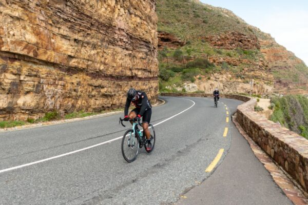 Two cyclists riding bikes along an empty mountain road to fundraise money for charity