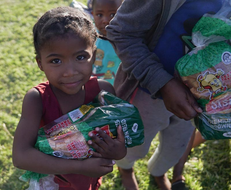 A young girl holds onto a SASKO bag full of peanut butter and jam sandwiches that were donated on Mandela Day 2020