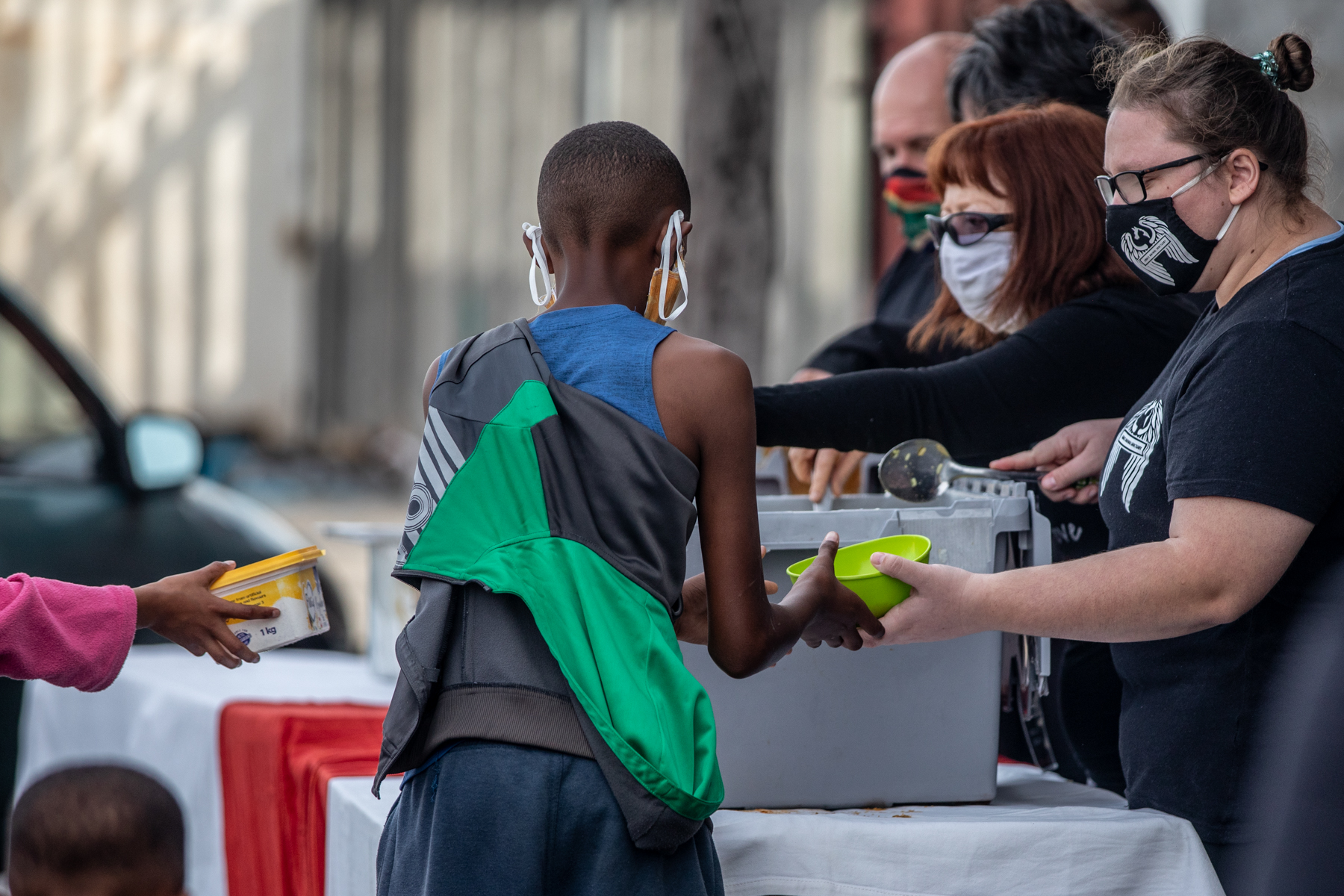 Boy with back to camera receives fresh soup from masked volunteers
