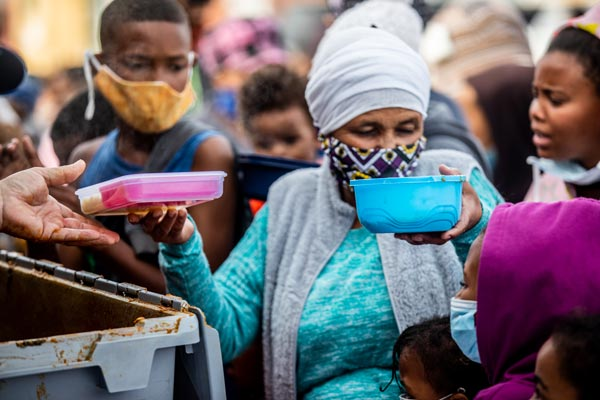 Woman at a soup kitchen wearing a facemask with plates of food in each hand