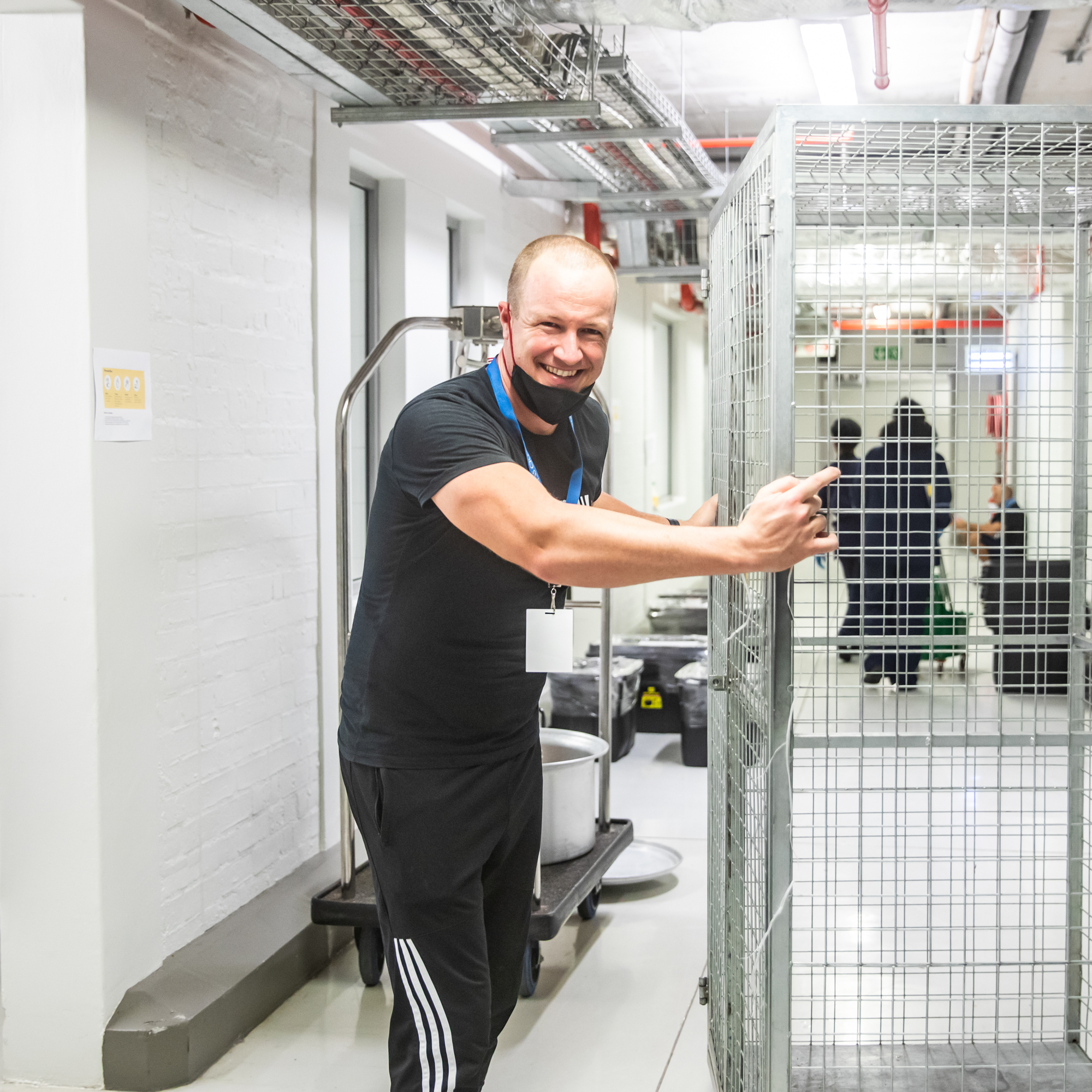 Smiling volunteer pushes an empty trolley through the Ladles of Love warehouse