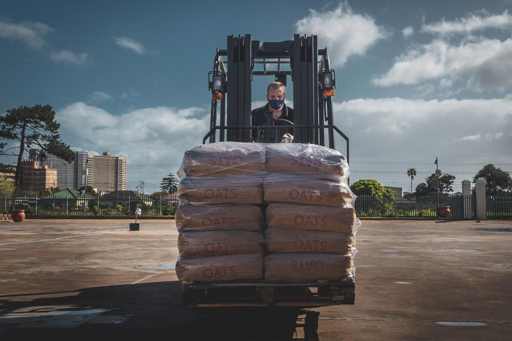 Goscor forklift loaded with oats driven by man across the Ladles of Love grounds