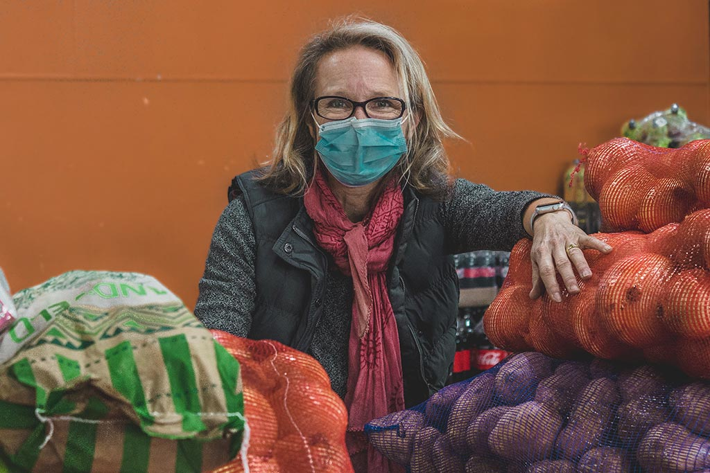 Ladles of Love staff member looks into camera wearing glasses and facemasks, behind vegetables