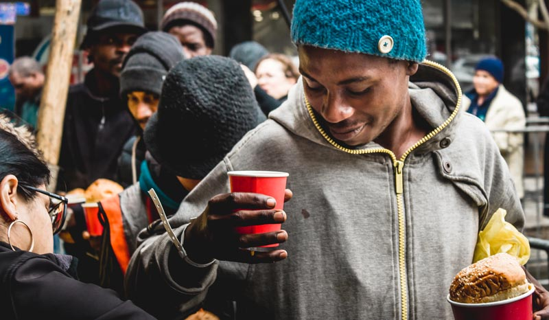 Guest at a soup kitchen smiles as he receives a bowl of soup, a bread roll and a cup of juice