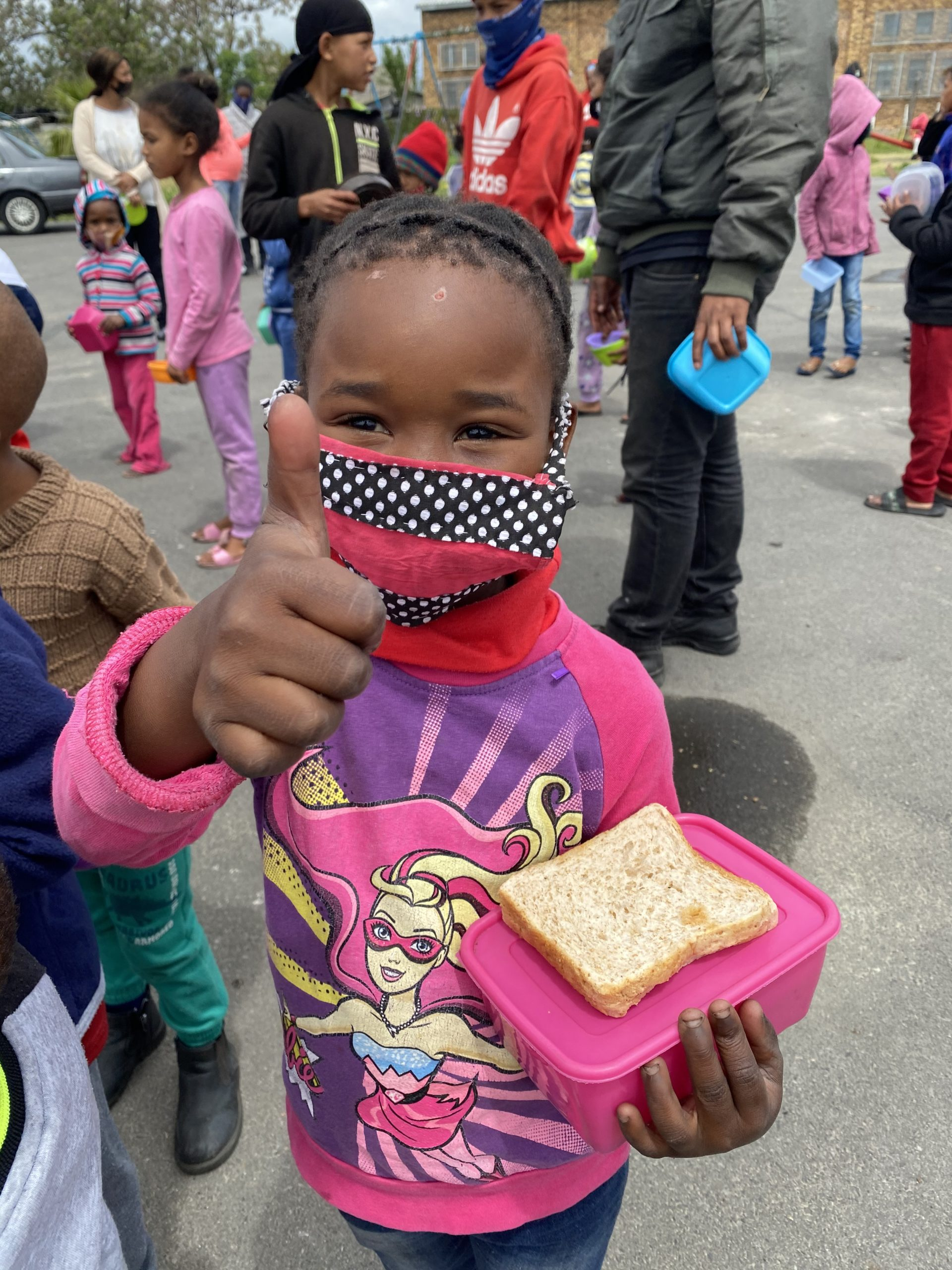 Child in facemask and pink superhero sweater gives a thumbs up to the camera, holding a sandwich