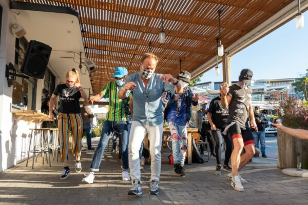 Group of people dancing outside together as a fun way to fundraise for charity