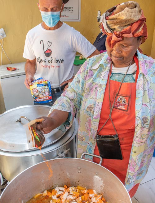 Mama Victoria seasons a pot of soup she's cooking in her community kitchen, with Ladles of Love founder Danny by her side
