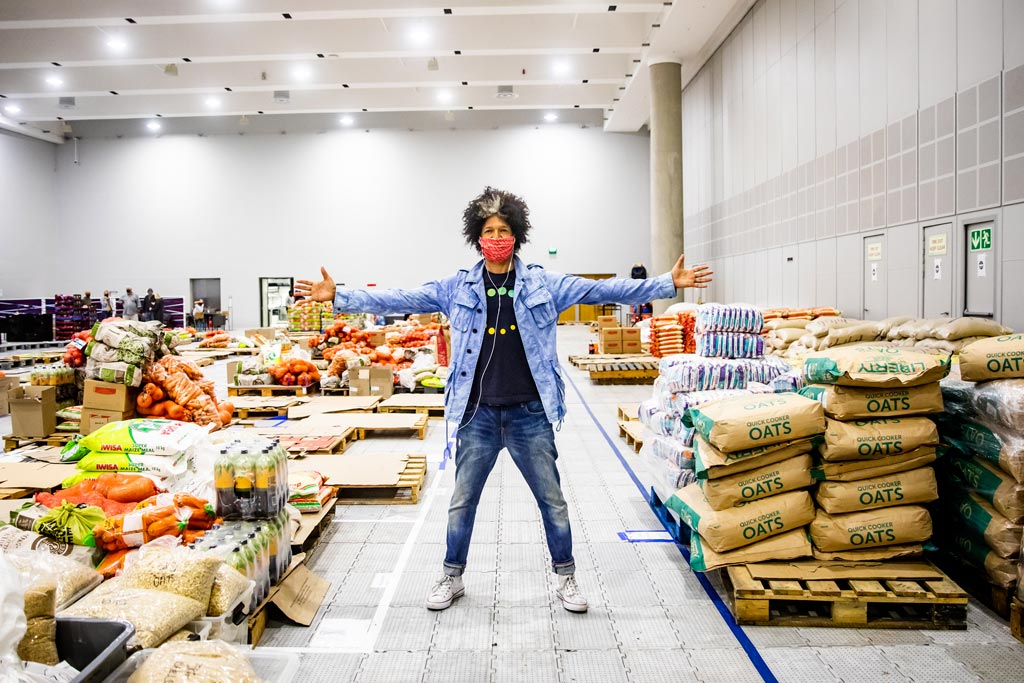 Comedian Marc Lottering stands with his arms out in the Ladles of Love warehouse, showing off the fresh produce donations
