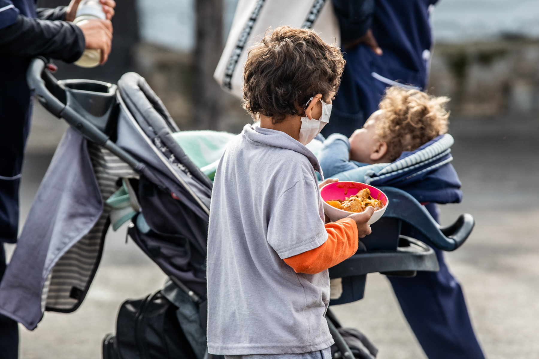 A boy holds a bowl of food as he walks next to a baby in a stroller
