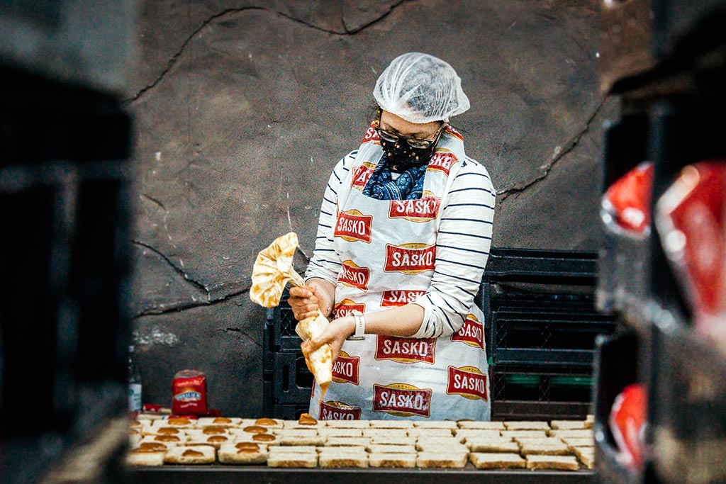A volunteer in a SASKO apron pipes peanut butter into sandwiches as part of a Ladles of Love charity team building event