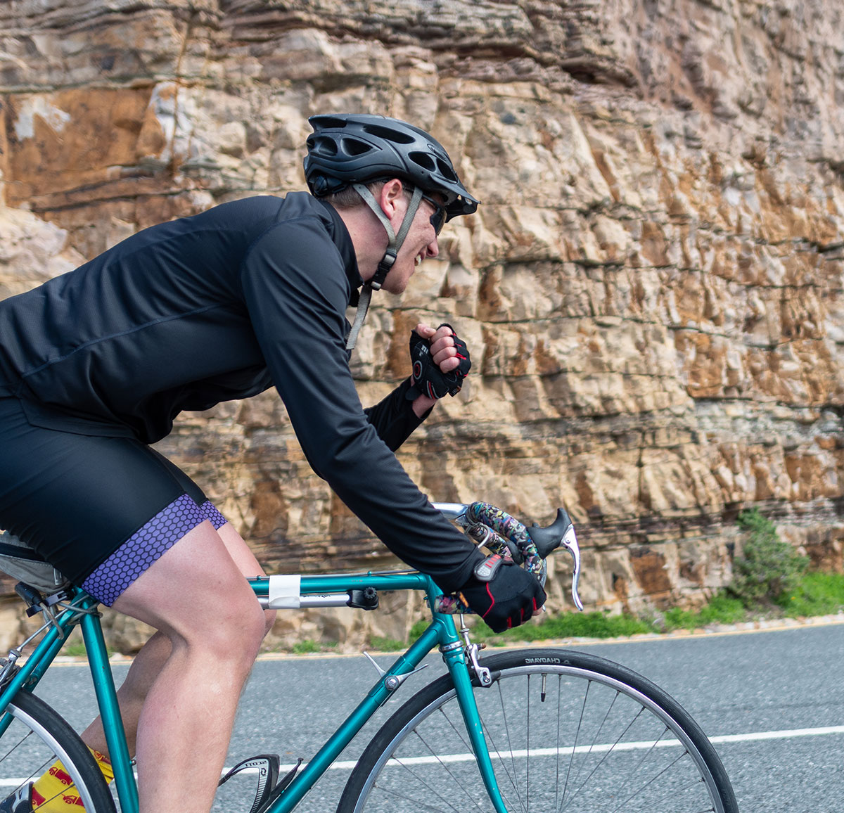Male cyclist on his bike punches the air triumphantly as they ride past rock formations