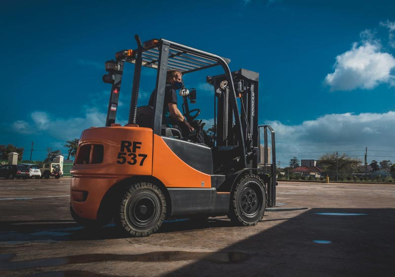 A man drives a forklift on loan from Goscor, a business supporting charities like Ladles of Love