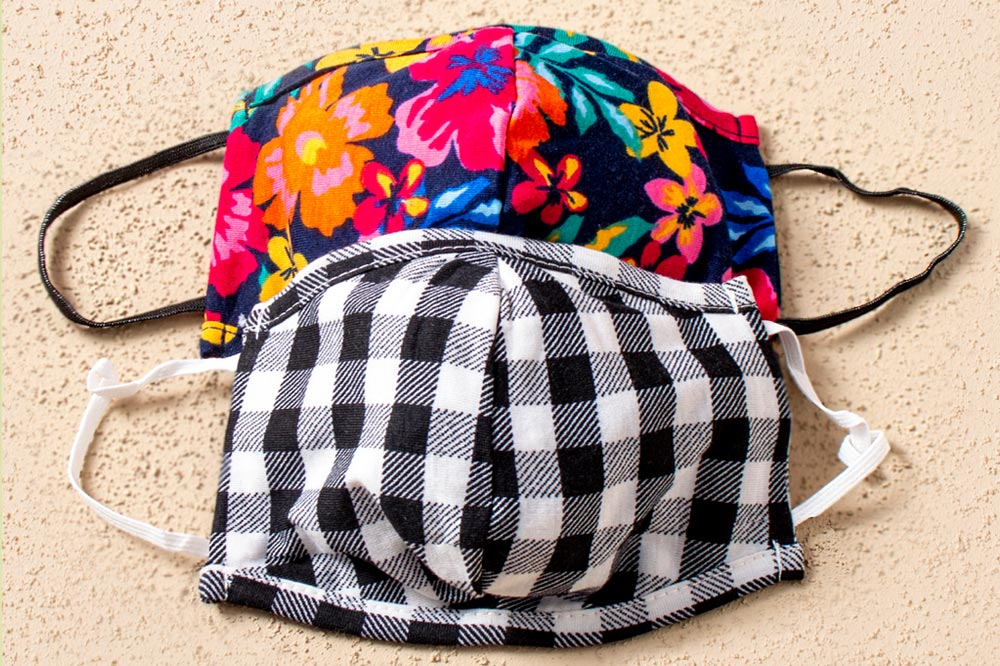Facemasks sold to raise funds for Ladles of Love include this black and white checked mask & bright floral print mask