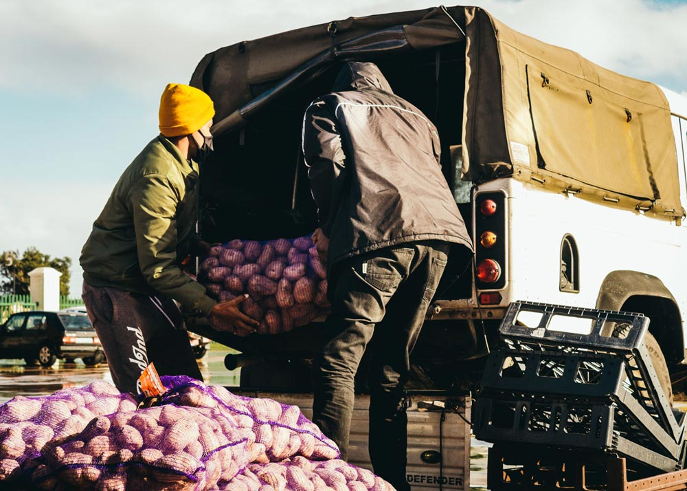 Two men, wearing jackets and hats, loading sacks of potatoes into a backie