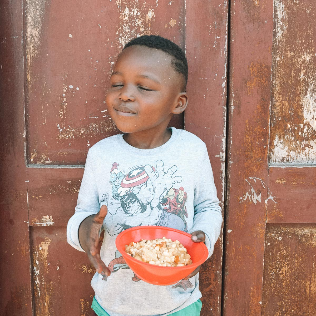 south african boy smiling over bowl of fresh and nutritious food