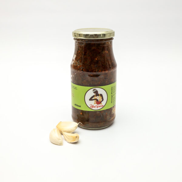 A jar of Chomoliya Kale Pickles with a green label from Ujuspice Morogo an African brand of food and has a picture of woman wearing yellow