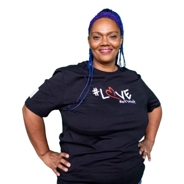 a woman with blue hair smiling and wearing a black t-shirt with the Ladles of Love Love Activist logo in white and red emblazoned across it