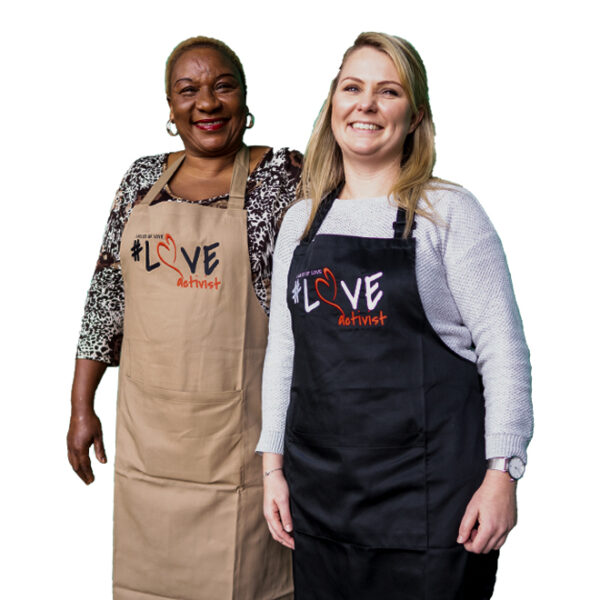 two women standing and smiling with the new ladles of love quality aprons that comes in two colours of black and khaki