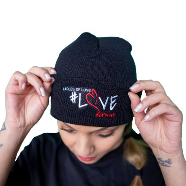 woman standing with her hands on a stylish branded black beanie from the ladles of love merchandise collection