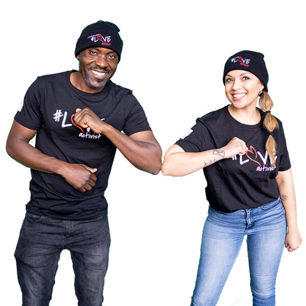 a man and woman smiling, knocking elbows and wearing a black t-shirt with the Ladles of Love Love Activist logo in white and red emblazoned across it