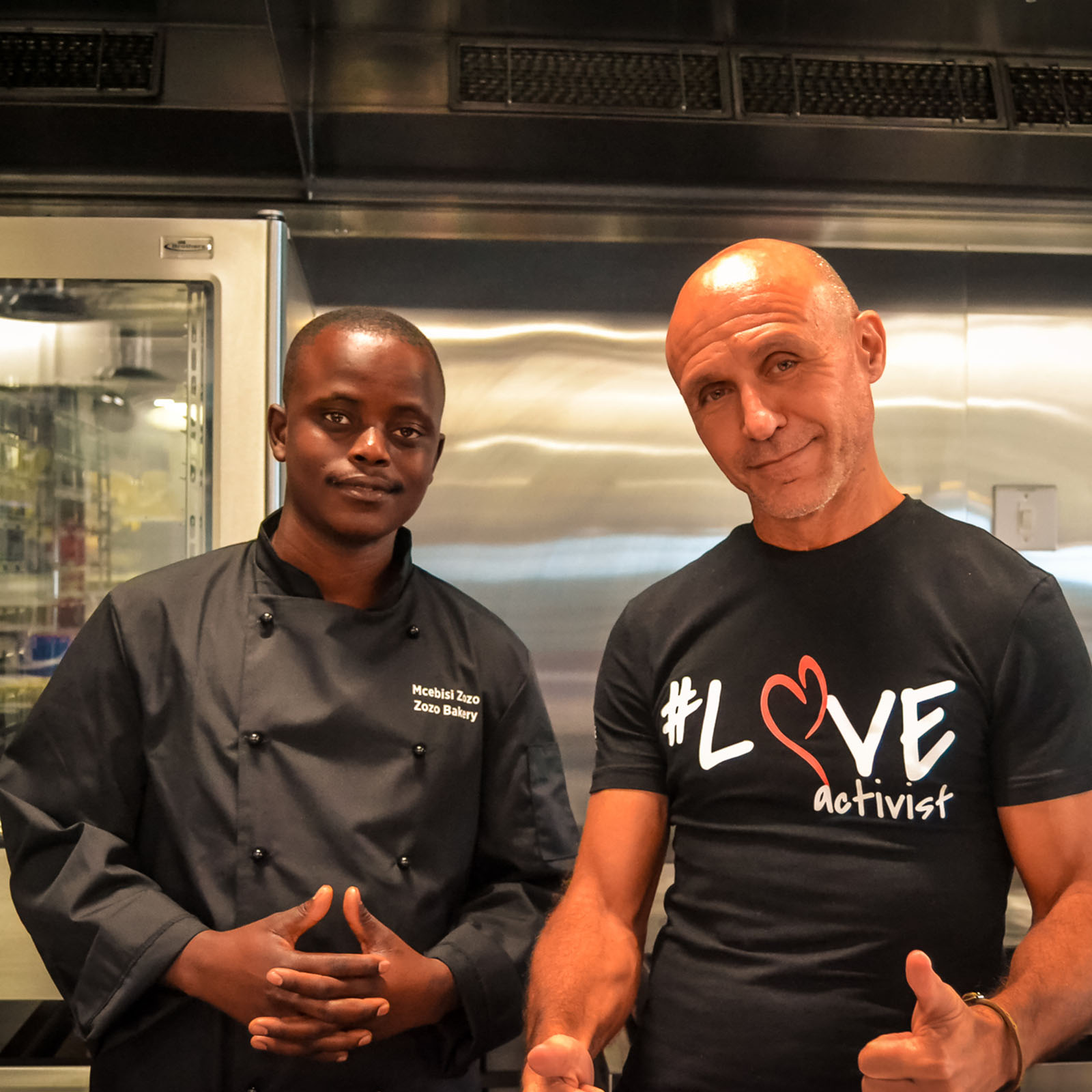 Danny, Ladles of Love founder, standing with young food entrepreneur and baker, Mcebisi in a kitchen.