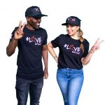 a man and woman standing smiling wearing casual clothes and black ladles of love peak caps and tee shirts