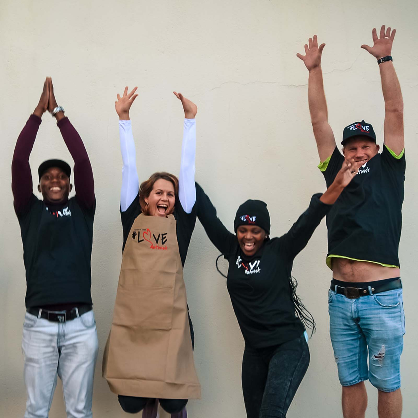 Group of south african people smiling, making heart shapes and standing with ladles of love branded clothing for the new online store where you can shop for charity