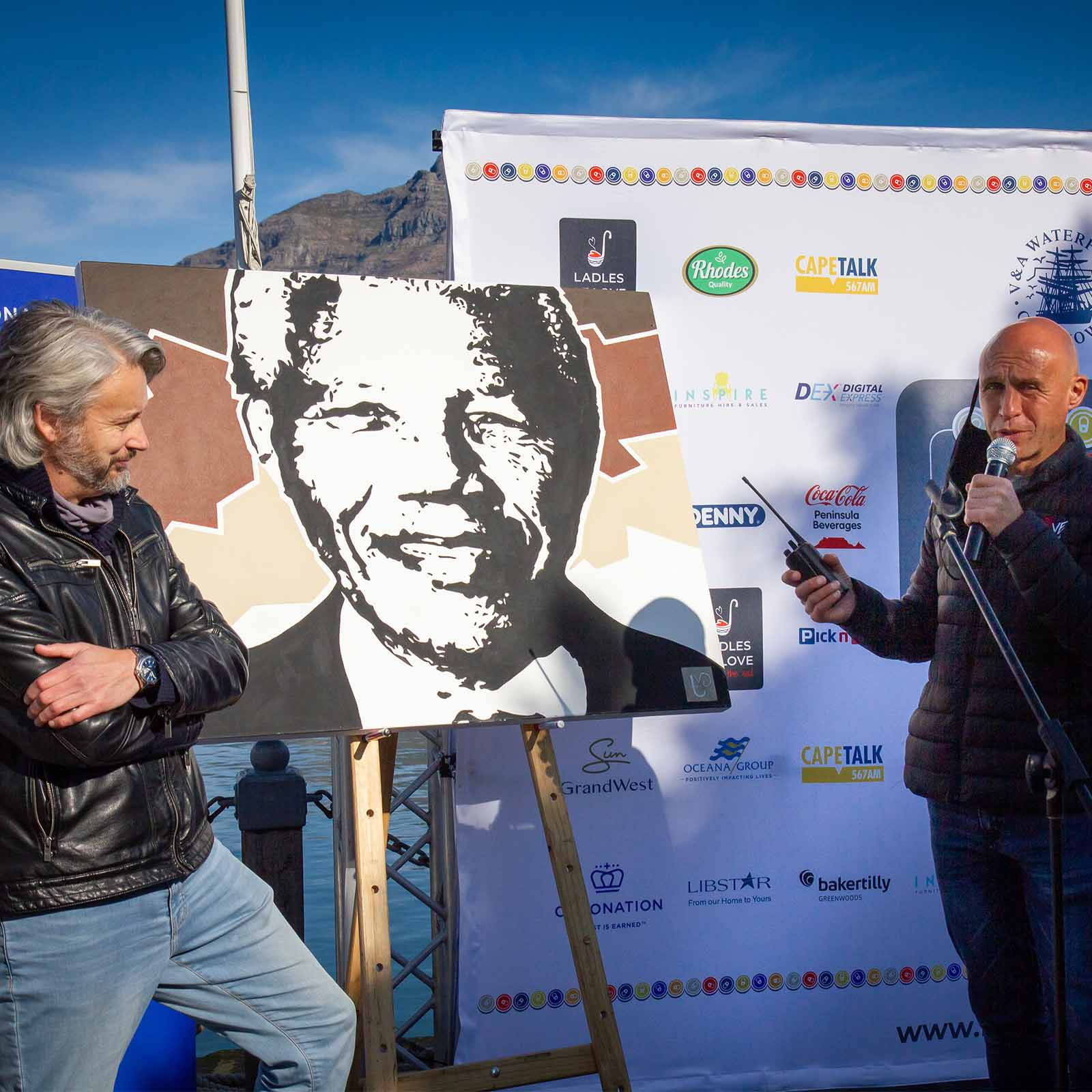 Founder Danny Diliberto standing with artists Tertius Van Wyk and his painting of Nelson Mandela showing how heritage day is celebrated today in South Africa
