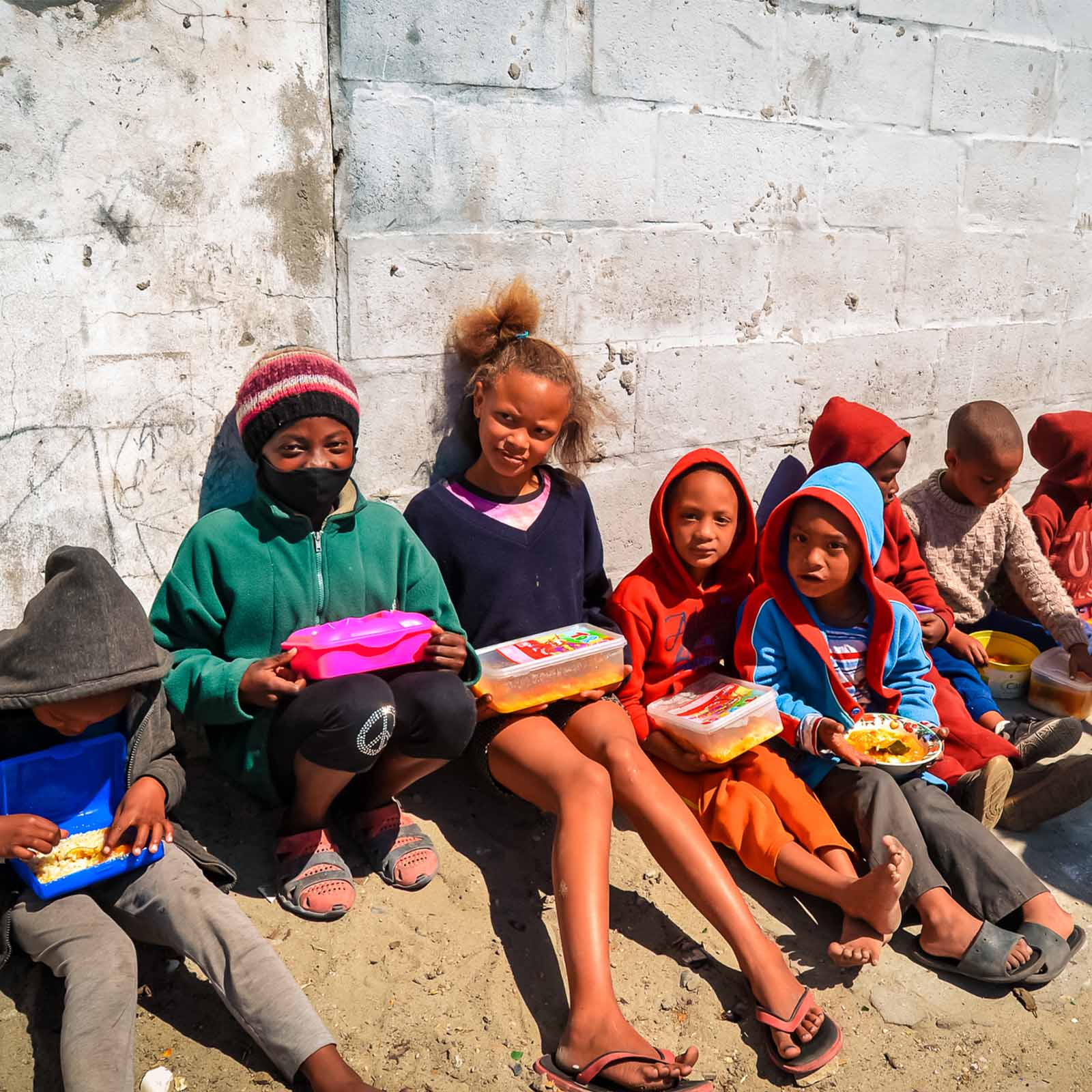 a line of hungry young children from poor areas in Cape Town who rely on sustainable living charities to help grow more food for their meals