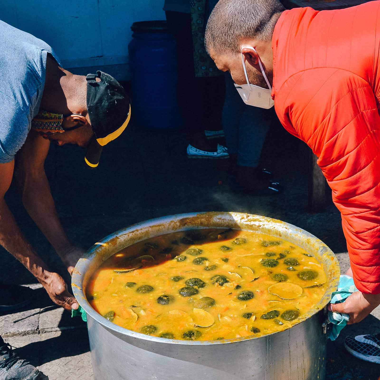 men holding a big pot of vegetable stew at a soup kitchen in cape town who rely on sustainable living charities to help grow more food