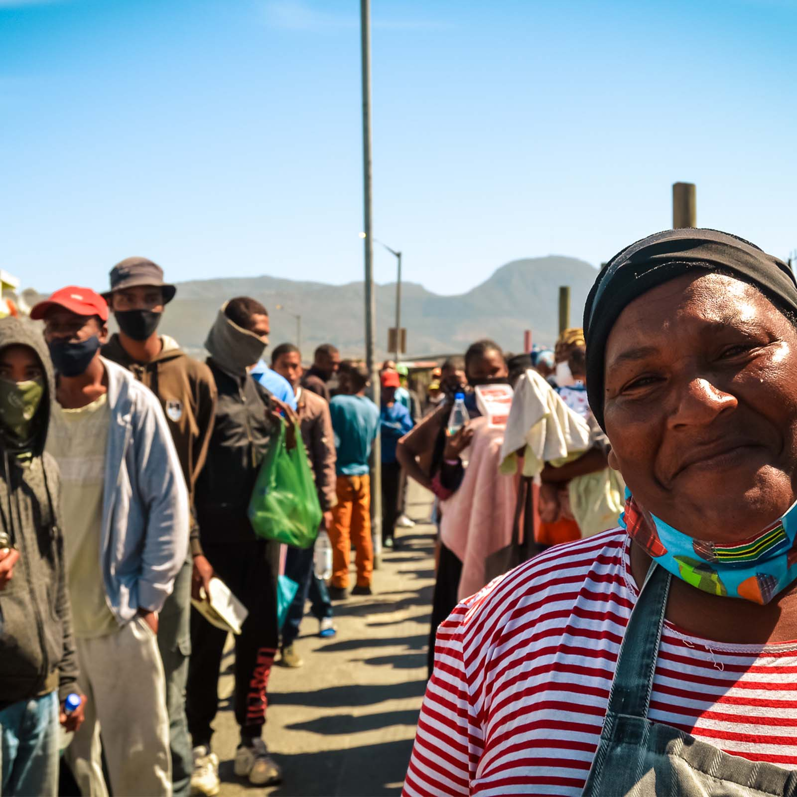 a long line of hungry people at the soup kitchen in cape town who need sustainable living charities to help them