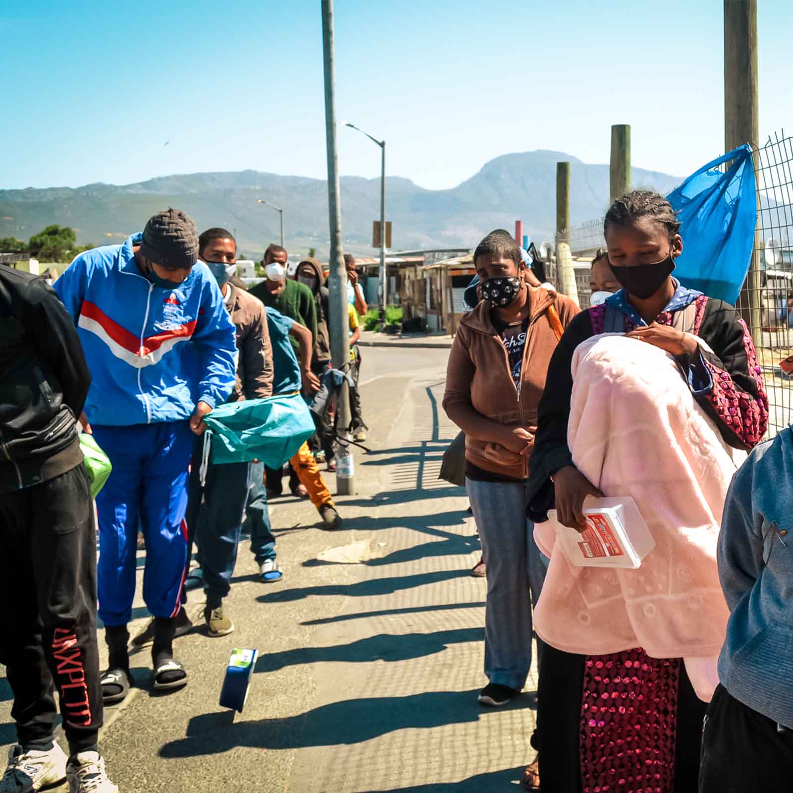 a long line of people from a poor community in the cape waiting for their meals at the soup kitchen that need urban vegetable farming for the meals