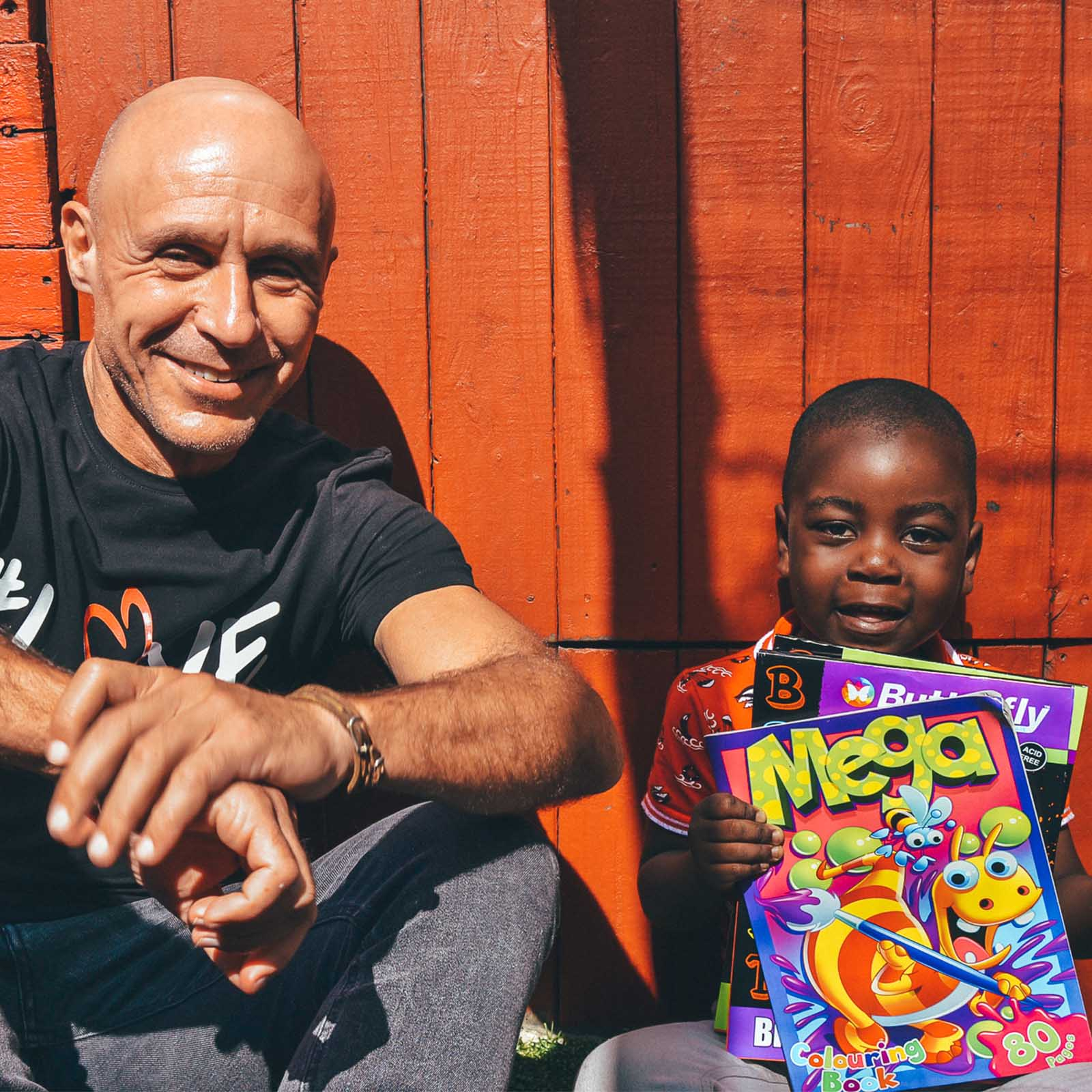 ladles of love founder danny diliberto sits with young boy at a cape town ecd who wants to end malnutrition in children