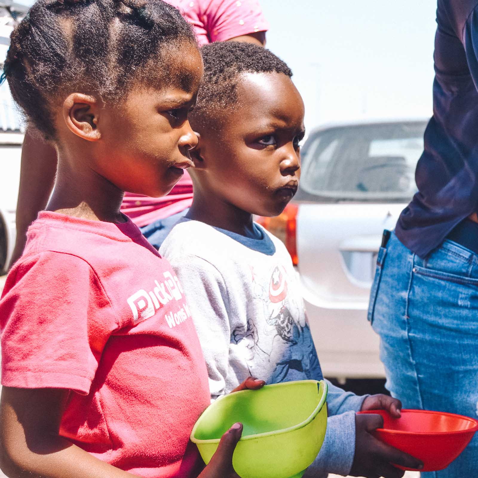 two children standing in line at a soup kitchen with their bowls waiting to be served to show why we must end malnutrition in children
